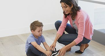 mom helping son tie his shoe